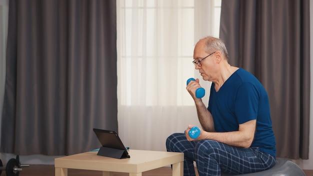 オンラインフィットネスプログラム中にダンベルでワークアウトを楽しんでいる年配の男性。老人年金受給者が自宅でヘルスケアスポーツを健康的に訓練し、高齢者でフィットネス活動を行う