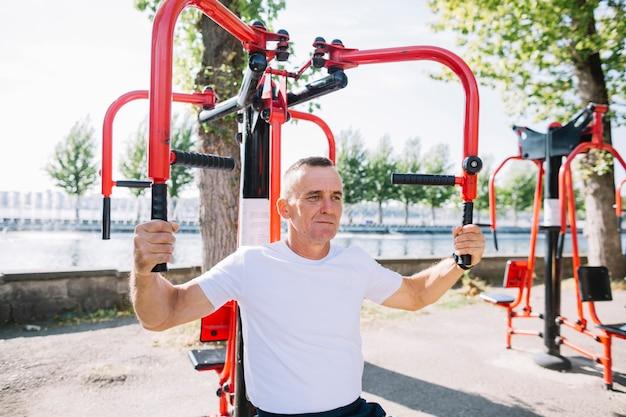 Senior man exercising arms muscles