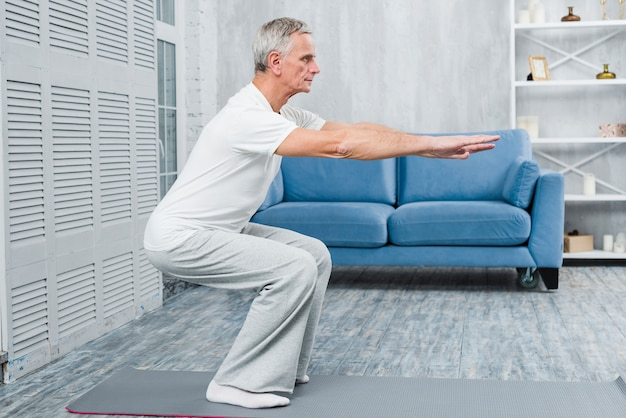 Senior man exercising at home