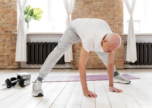 屋内で運動する年配の男性