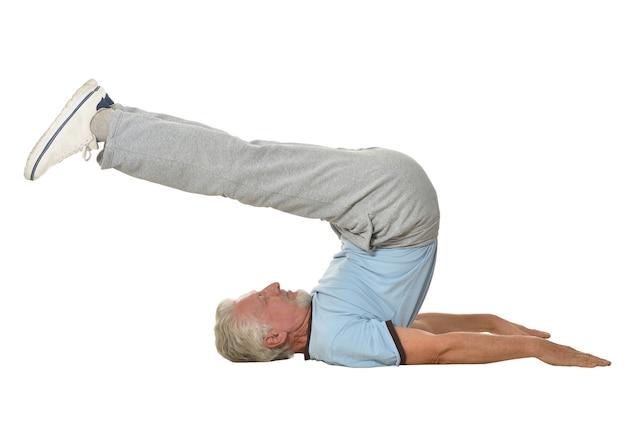 白い背景で運動する年配の男性