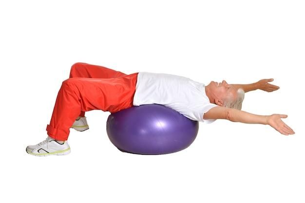 白い背景の上のボールで運動する年配の男性