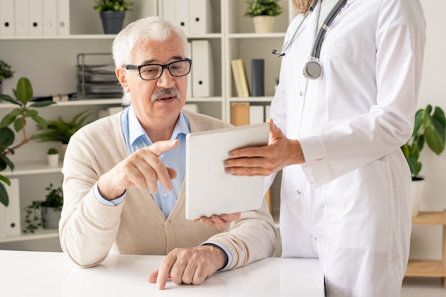 Senior man in eyeglasses and casualwear pointing at display of tablet held by doctor while looking through his medical indications