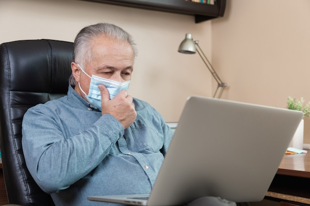Senior man in face mask working or communicate on laptop at home. study, training, work, communication, entertainment, leisure during the coronavirus period.