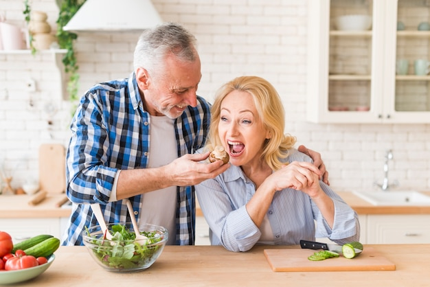 Senior man feeding the mushroom to her wife in the kitchen