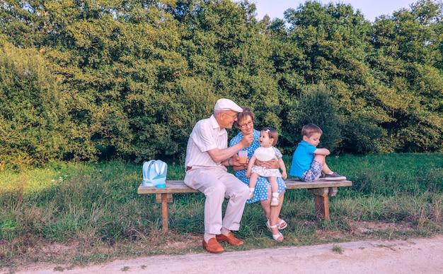 Старший мужчина кормит очаровательную девочку фруктовым пюре, в то время как ревнивый брат поворачивается спиной, сидя на скамейке на открытом воздухе. концепция отношений бабушек и дедушек и внуков.