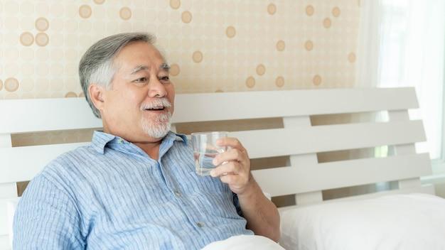 노인은 아침에 신선한 물을 마시는 것이 행복하다고 느끼며 집 실내 배경에서 시간을 즐기고 있습니다 - 라이프스타일 노인 행복 개념