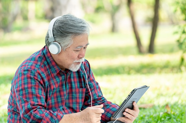 Senior man feel happy enjoy listening to music with earphones headphones isolated