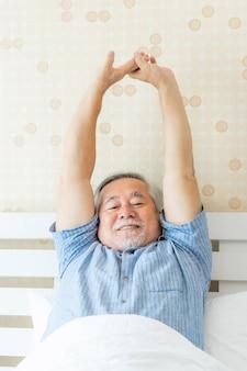 年配の男性は、彼の家の屋内寝室の背景で時間を楽しんで朝に目覚める幸せな健康を感じます-ライフスタイルシニア幸せの概念
