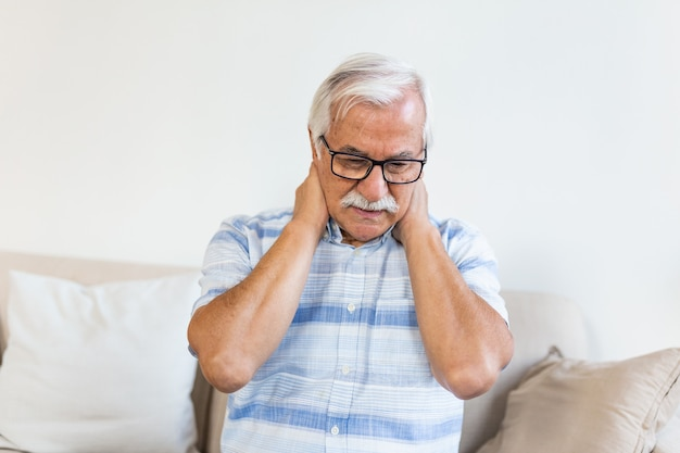 Senior man feeling exhausted and suffering from neck pain