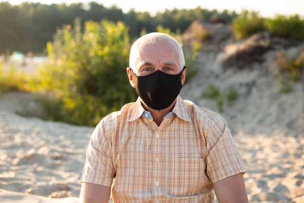 Senior man feeling sick, wearing protective mask against transmissible infectious diseases and as protection against the flu