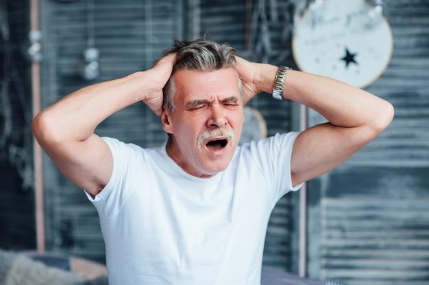 Senior man feeling sleepy and yawning in his bedroom, holding on head