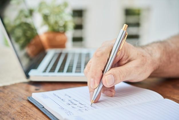 Senior man filling diary