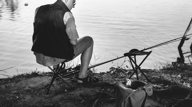 Старший мужчина, рыбалка на берегу озера