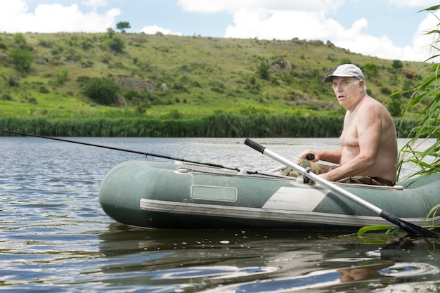 Senior man fishing from a rubber dinghy
