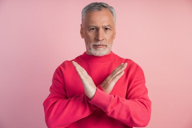 ピンクの壁に身振りで示す年配の男性