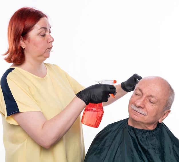 Senior man getting a haircut. woman wetting  hair before cutting