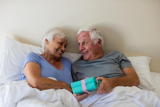 自宅の寝室で女性にサプライズギフトを与える年配の男性