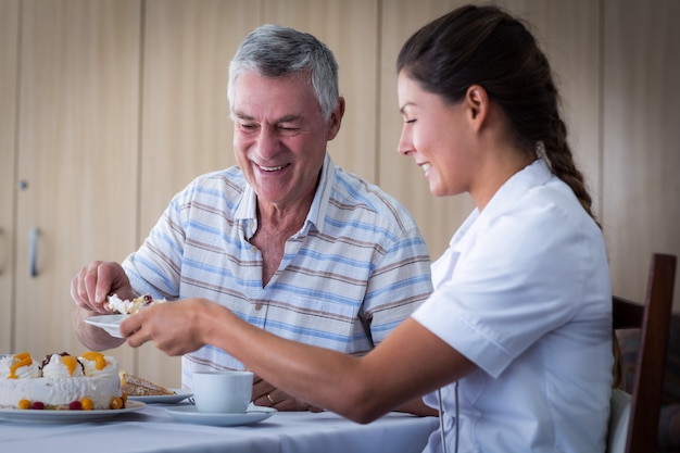 Senior man giving cake to doctor in living room