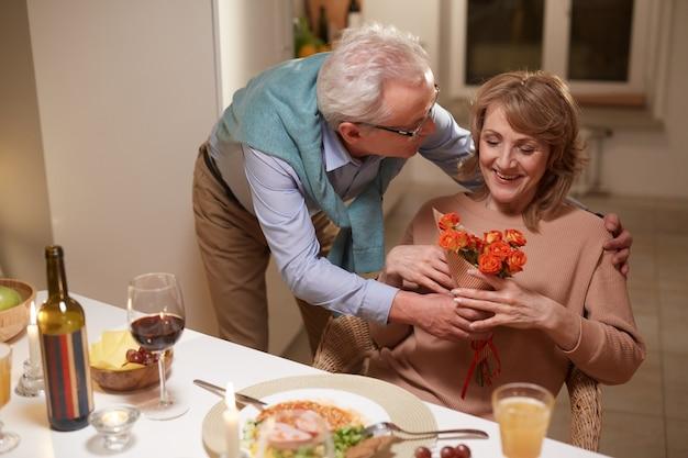 Старший мужчина дарит цветы своей жене и поздравляет ее с годовщиной во время ужина