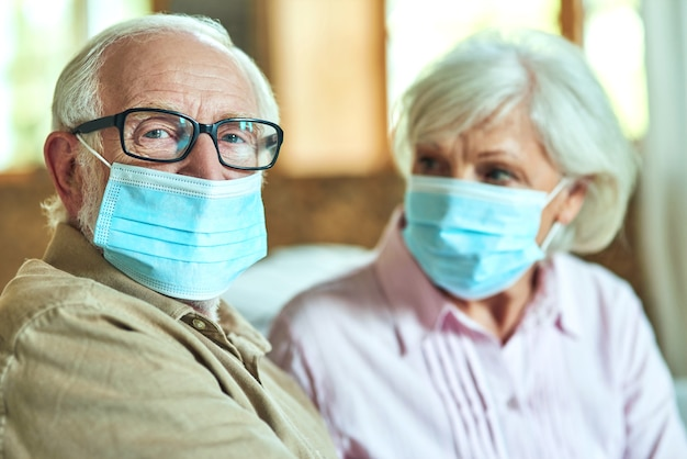 Senior man in glasses sitting next to his wife and using masks