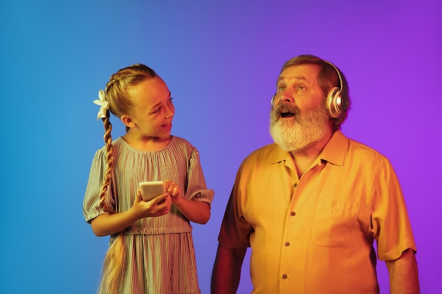Senior man and granddaughter on neon surface