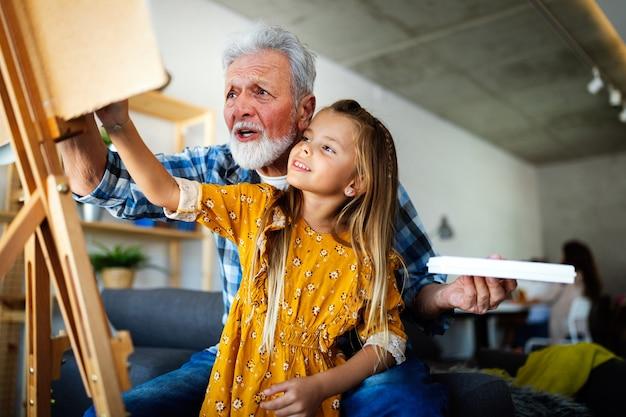 Старший мужчина, дед и его внук рисуют, вместе рисуют. счастливое семейное время