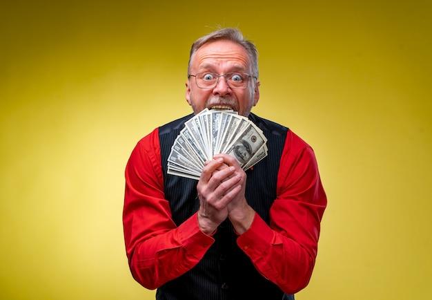시니어 남자는 노인의 얼굴 근처에서 돈의 팬인 복권에 당첨되었습니다.