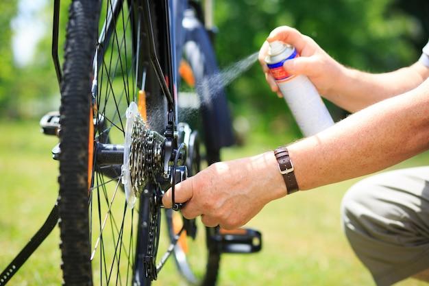 Старший мужчина руки распыляет масло на цепь от колесного велосипеда