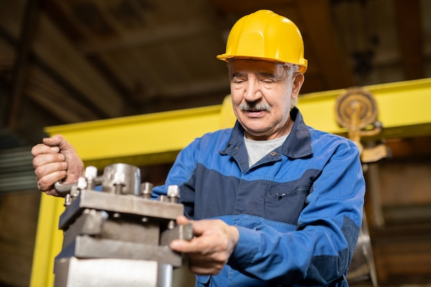 Senior man in hardhat and uniform checking condition of iron generator of large industrial machine