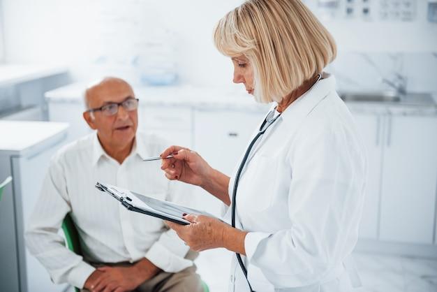 Старшего мужчину консультирует в поликлинике женщина-врач.