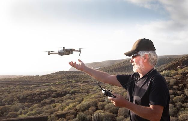 시니어 남자는 산맥에서 드론을 가지고 즐거운 시간을 보낸다. 석양 아래 비행을 찾고. 흰 머리와 수염을 가진 캐주얼한 백인 1명