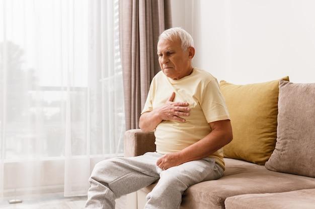 年配の男性は胸が痛い。酸逆流症や心臓発作などのさまざまな問題の概念。