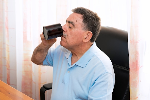 コーヒーを持って、彼のコンピュータで働いている上司