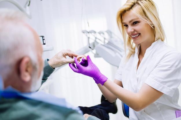 歯科医院で歯科治療を受けている年配の男性。