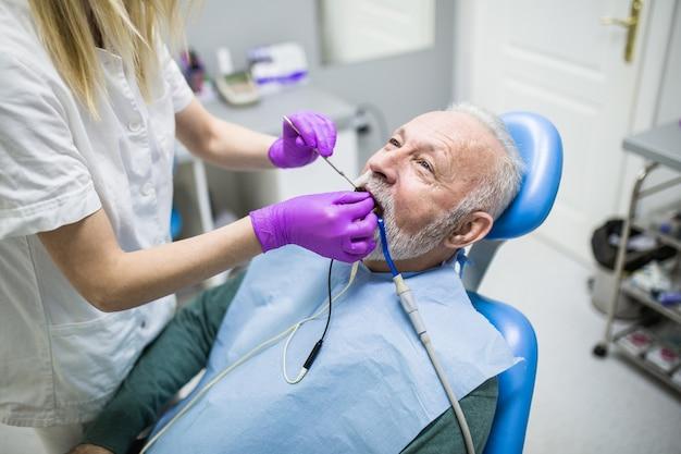 치과 의사의 사무실에서 치과 치료를 받는 수석 남자.