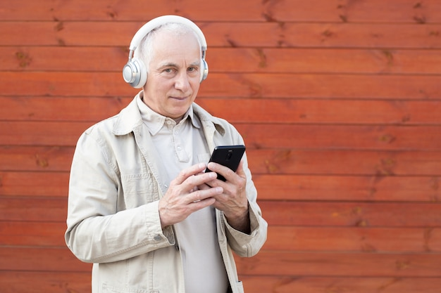 Senior man having fun using mobile smartphone and wearing headphones. happiness, technology and elderly lifestyle people concept