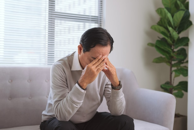 Senior man having headache while sitting on couch at home.