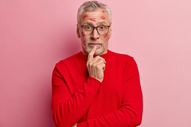 Uomo maggiore che ha macchie di rossetto sul viso e indossa un maglione rosso