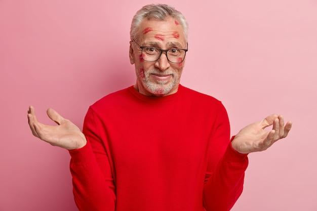 顔に口紅の染みがあり、赤いセーターを着ている年配の男性