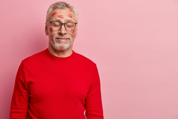 Старший мужчина в красном свитере с пятнами помады на лице
