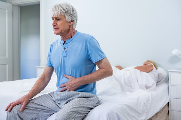 Senior man having stomach pain while sitting on bed