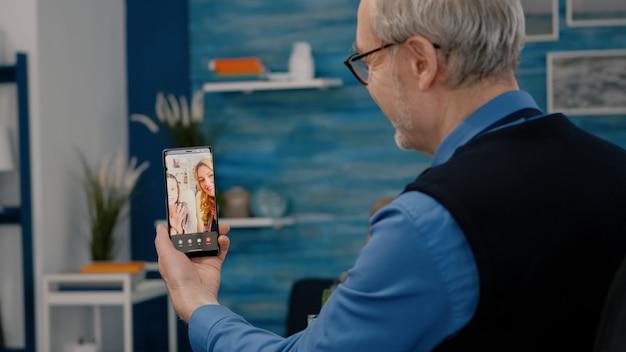 Uomo anziano che fa una videochiamata online parla con il nipote usando lo smartphone seduto in soggiorno in pensione