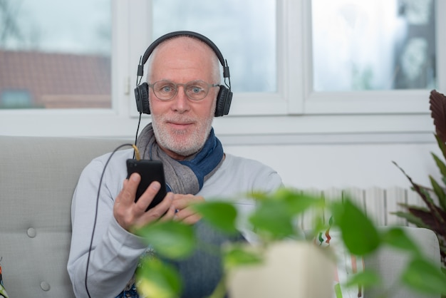 Senior man in headphones listening to music at home