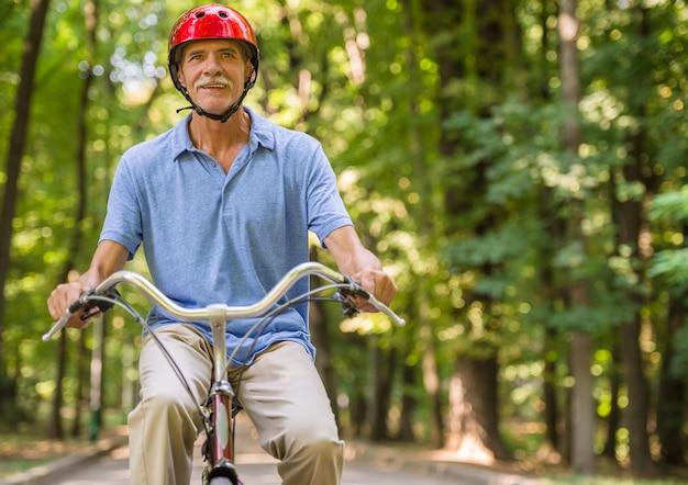 Senior man in helmet is riding bicycle in park.