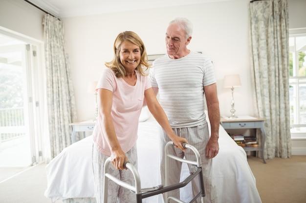 Старший мужчина помогает женщине ходить с ходунками
