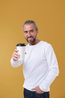 一杯のコーヒーを持っている年配の男性