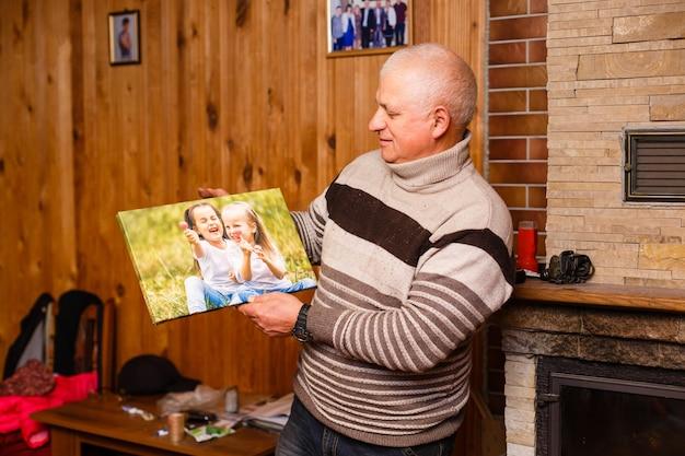 손자의 사진 캔버스를 들고 있는 노인