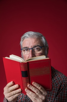 Senior man holding book in front of his face against red backdrop
