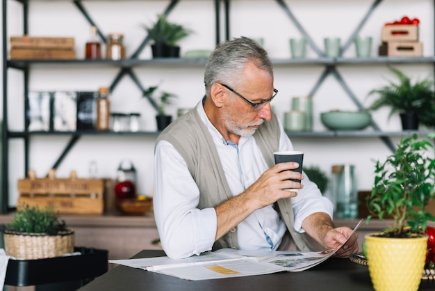 Senior man holding coffee cup in hand reading newspaper